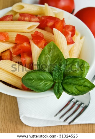 Italian pasta with tomato and basil on the table