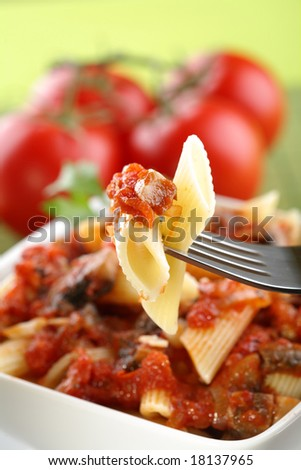 Italian pasta with tomato sauce and parmesan on fork.