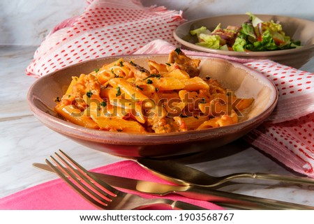 Italian penne alla vodka pink cream sauce with sliced spicy sausage and side salad ストックフォト ©