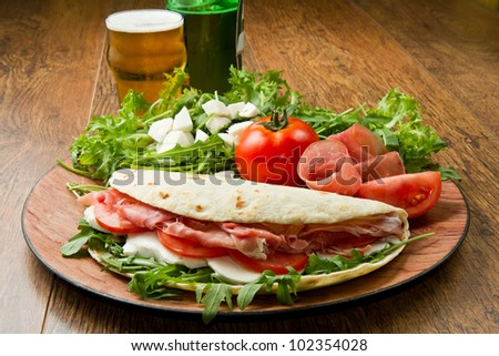 italian piadina with ham, fresh salad and mozzarella cheese