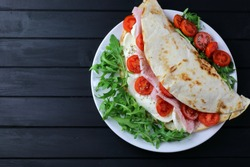 Italian piadina with ham, mozzarella, rocked salad and tomatoes on black wooden