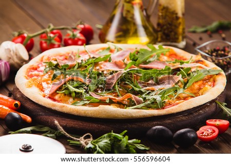 Italian pizza with chicken, onions and rucola leaves