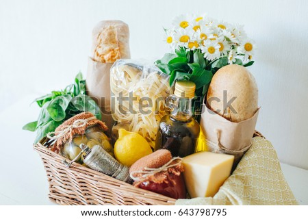 Italian products. Italian traditions. Ingredients. Healthy food. Basket with products. Basket with a gift. Food delivery. A food set. White wooden table. Stock photo ©