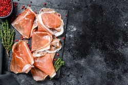 Italian prosciutto crudo with thyme, cured ham. Black background. Top view. Copy space