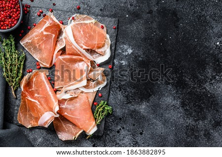 Italian prosciutto crudo with thyme, cured ham. Black background. Top view. Copy space Foto stock ©