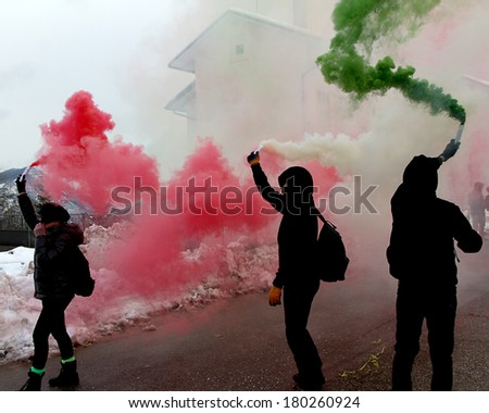 italian protest with protesters wearing black gloves with green red and white smoke