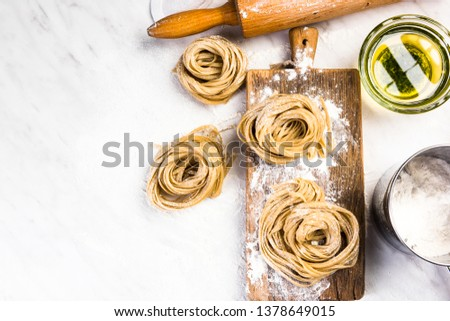 Italian raw uncooked tagliatelle pasta on white marble table.