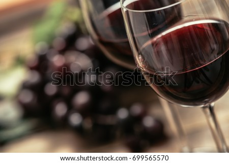 Italian red wine tasting and wine culture: wine glass and grape on a rustic wooden table #699565570