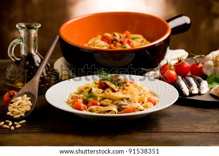 Italian regional dish made of pasta with sardines on wooden table