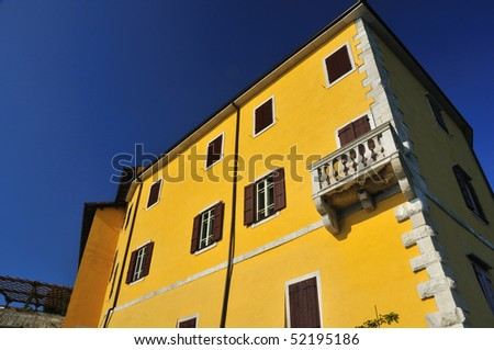 italian renaissance castle with yellow walls and shuttered windows at Duino in Italy