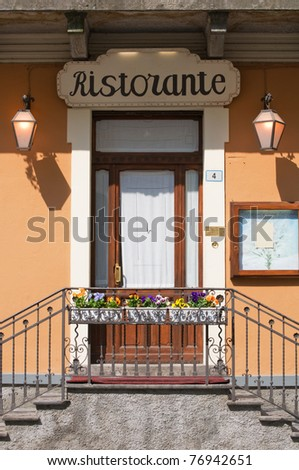 Italian restaurant door with stairs,flowers and blank menu on display