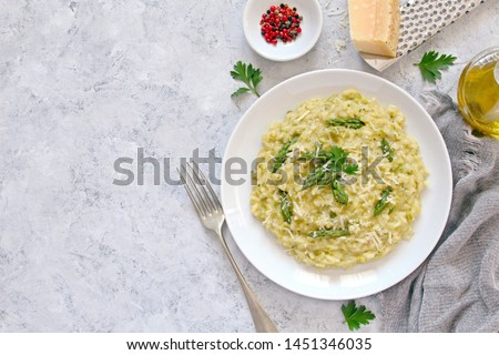 Italian risotto with spring asparagus and parmesan cheese on light background. Top view with copy space.