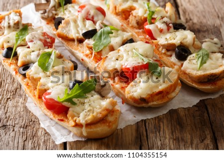 Italian sandwiches pizza casserole: cut baguette baked with chicken, cheese, tomatoes, olives and mushrooms close-up on the table. horizontal