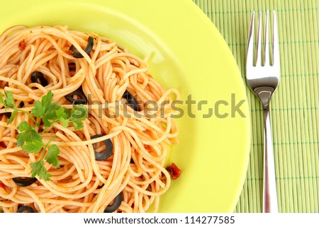 Italian spaghetti in plate on bamboo mat close-up