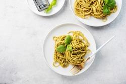 Italian spaghetti with pesto sause and parmesan cheese, flatlay image