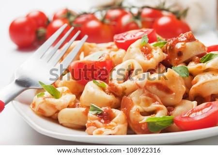 Italian tortellini pasta with tomato sauce and basil - stock photo