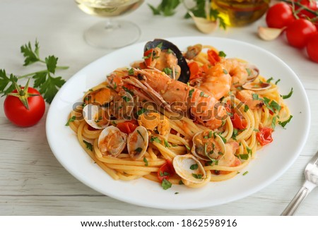 """Italian Traditional Dish""""Spaghetti allo Scoglio"""" or """"Spaghetti with Seafood"""", spaghetti with mixed seafood,olive oil,garlics,white wine,cherry tomatoes,parsley and peppers on white plate"""