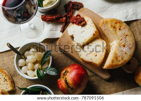 Italian Tuscan wooden table full of typical dishes, salami, cheese, vegetables and red chianti wine in a Classy and stylish environment