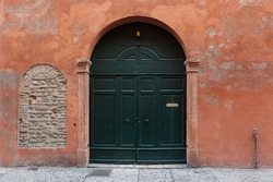 Italian urban architecture, green wooden arched doorway against rustic red ochre wall
