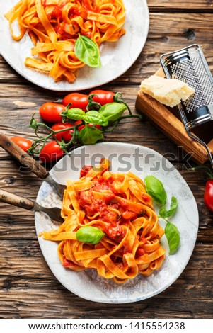 Italian vegetarian pasta fettuccine with tomato and basil, selective focus