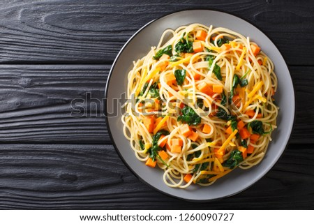 Italian vegetarian spaghetti with pumpkin, spinach and cheddar cheese close-up on a plate on the table. horizontal top view from above