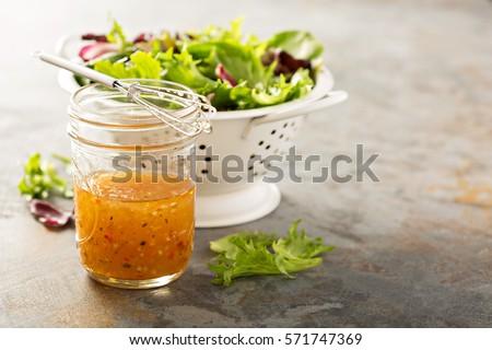 Shutterstock Italian vinaigrette dressing in a mason jar with fresh vegetables on the table