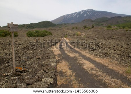 Italian wooden direction pointers for hikers with route name, number, places, location and distance. Hiking tour trail, through the lava fields of the national park #1435586306