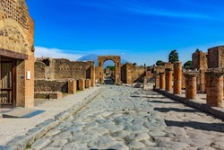 Italy. Ancient Pompeii (UNESCO World Heritage Site). Paving stones of Via del Foro. There is Arch of Caligula, Via di Mercurio and Mount Vesuvius in the background