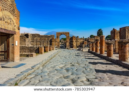 Shutterstock Italy. Ancient Pompeii (UNESCO World Heritage Site). Paving stones of Via del Foro. There is Arch of Caligula, Via di Mercurio and Mount Vesuvius in the background