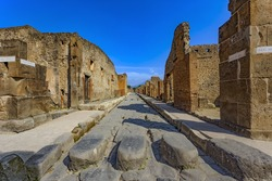 Italy. Ancient Pompeii (UNESCO World Heritage Site). Paving stones of Via Stabiana (Cardo Maximus street) with the blocks stone. There is Mount Vesuvius in the background