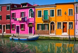 Italy. Burano Island. Brightly painted houses are reflected in the water channel