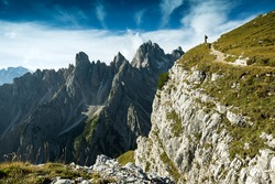 Italy, Dolomites - Man hiker standing very far from the edge of the barren rocks
