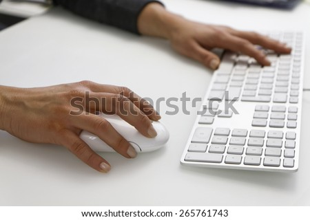 Italy, female hands on a computer mouse and keyboard