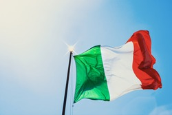 Italy flag in windy against a blue sky in the sun