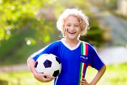Italy football fan. Italian kids play soccer on outdoor field. Cheering team fans celebrate victory. Children score a goal at football game. Little boy in Italia jersey kicking ball on outdoor pitch.