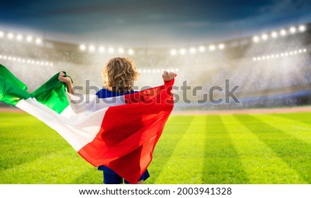 Italy football supporter on stadium. Italian fans on soccer pitch watching team play. Group of supporters with flag and national jersey cheering for Italia. Championship game. Forza Azzurri Foto stock ©