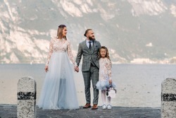 Italy, Lake Garda. Beautiful family on the shores of lake Garda in Italy at the foot of the Alps. Father, mother and daughter in Italy