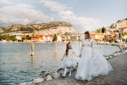 Italy, Lake Garda.Stylish Mother and daughter on the shores of lake Garda in Italy at the foot of the Alps. mother and daughter in Italy
