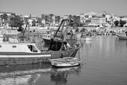 Italy, Mediterranean Sea, Sicily, Scoglitti (Ragusa Province); fishermen working on a wooden fishing boat in the port