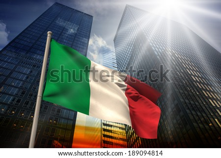 Italy national flag against low angle view of skyscrapers at sunset