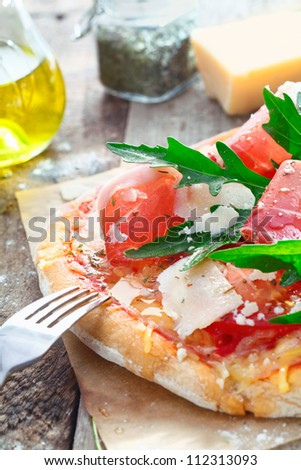 Italy Pizza Closeup with rucola, parmesan hard cheese and Parma ham on wooden background.