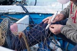Italy, Sicily, Mediterranean sea, Marina di Ragusa (Ragusa Province); fisherman repairing his nets on a fishing boat in the port