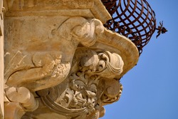 Italy, Sicily, Scicli (Ragusa province), ornamental statues under a balcony of the Baroque Beneventano Palace (18th Century a.C.)