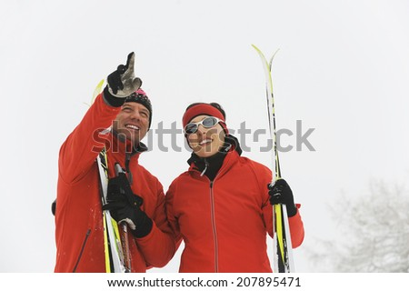 Italy, South Tyrol, Couple in ski wear, man pointing