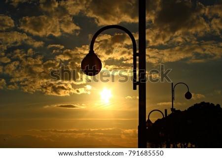 Italy: Street lamp in sunset.