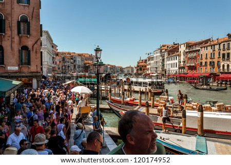 ITALY, VENICE - JULY 16: Crowd of tourist near Grand Canal on July 16, 2012 in Venice. More than 20 million tourists come to Venice annually.