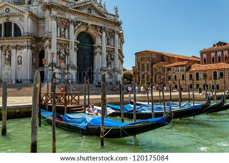 ITALY, VENICE - JULY 16: Gondolas moor on July 16, 2012 in Venice. Gondolas are traditional flat-bottomed rowing boats that today mainly carry tourists.