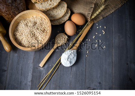 Items and ingredients for bread preparation on a wooden grey background. Flour, eggs, rolling pin, wheat grain, copy space.