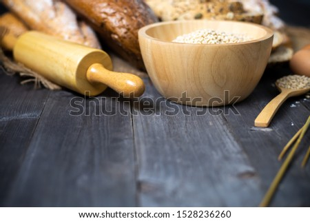 Items and ingredients for bread preparation on a wooden table,flour, rolling pin, wheat grain, copy space.