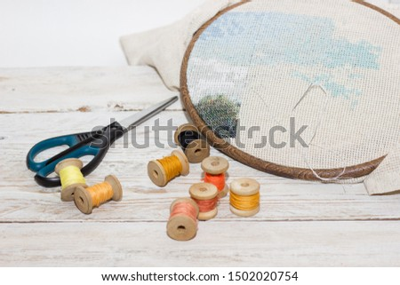Items for needlework. Items for embroidery on a white wooden table.